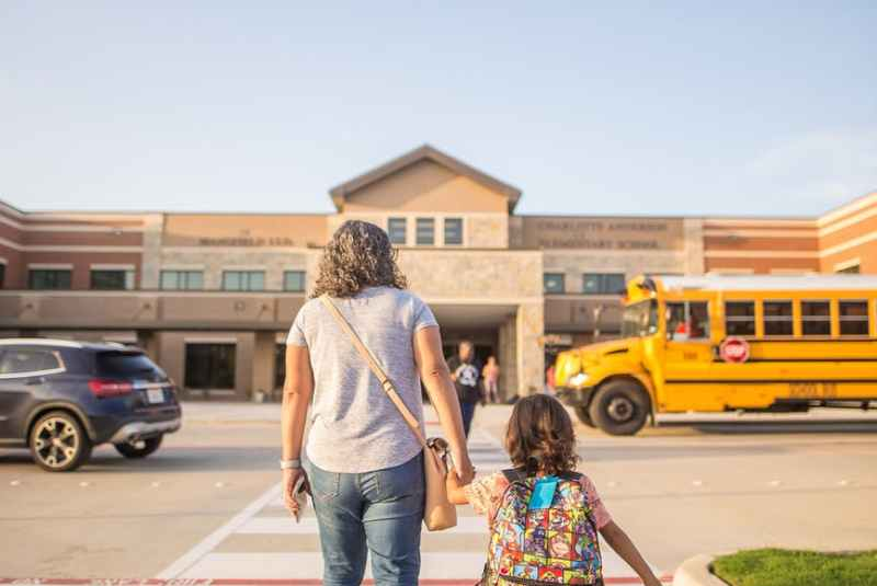 anonymous mother leading daughter to school in city